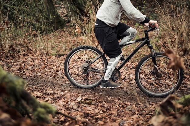 Fietser berijdende fiets op sleep in het bos Gratis Foto