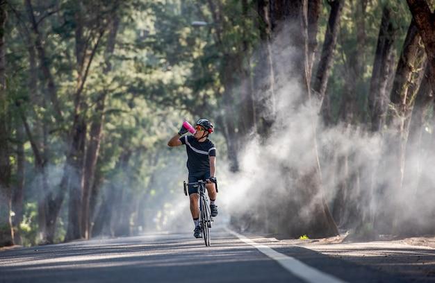 Fietser drinkt water uit de sportfles Premium Foto