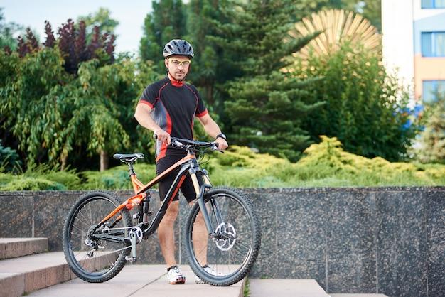 Fietser met fiets bij de trap Premium Foto