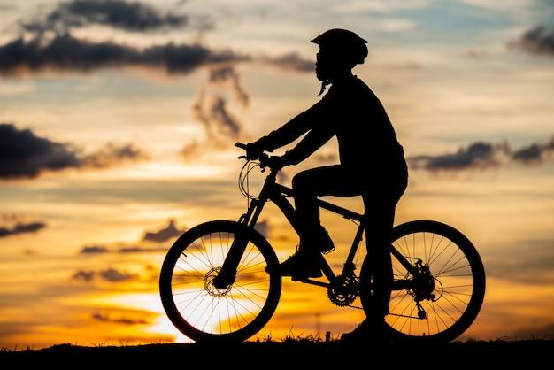 Fietser rustend silhouet bij zonsondergang. actief buitensportconcept Gratis Foto