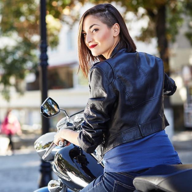 Fietsermeisje in een leerjasje op een motorfiets Gratis Foto