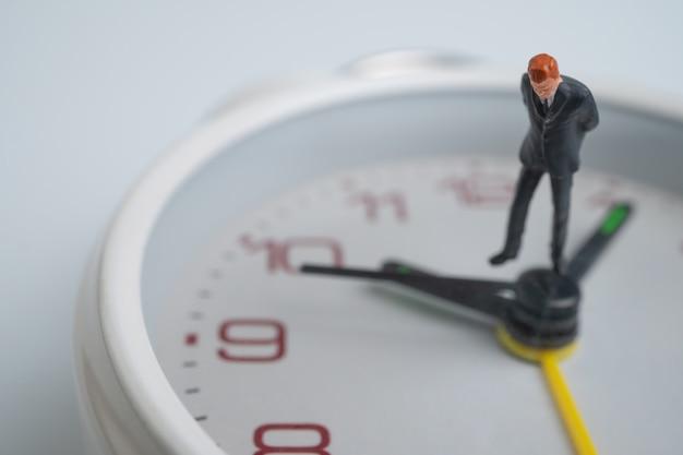 Figuur zakenlieden kijken en denken en staan op de witte wijzerplaat naast de wijzerplaat met de tijd. Premium Foto