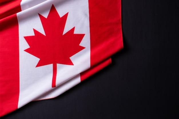 Fijne canada-dag. vlaggen van canada tegen een zwarte achtergrond. kopieer ruimte. Premium Foto
