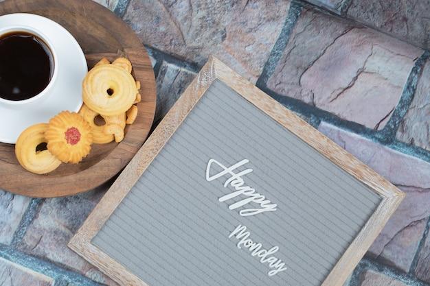 Fijne maandag op het bord met een kopje drank en koekjes eromheen Gratis Foto