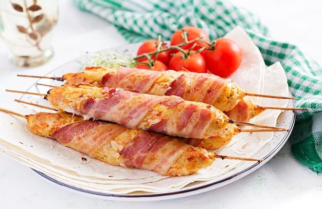 Fijngehakte lula kebab gegrilde kalkoen (kip) met pompoen omwikkeld met spek op plaat. Gratis Foto