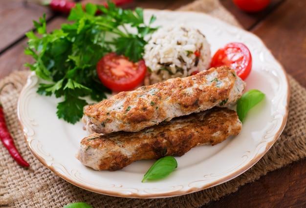 Fijngehakte lula kebab gegrilde kalkoen (kip) met rijst en tomaat. Gratis Foto