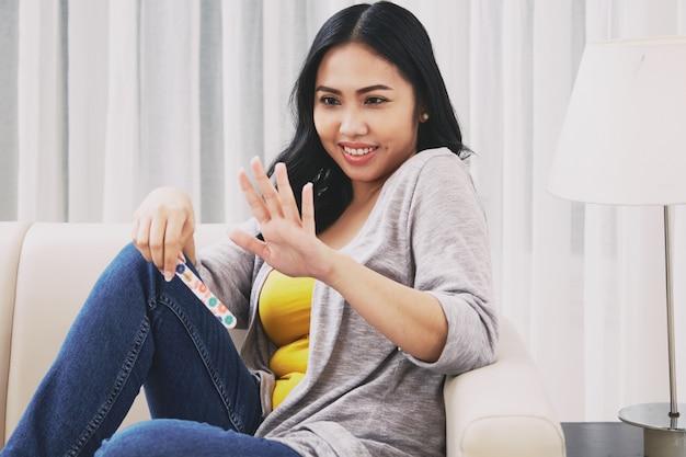 Filipijnse vrouw die vingernagels bekijkt Gratis Foto