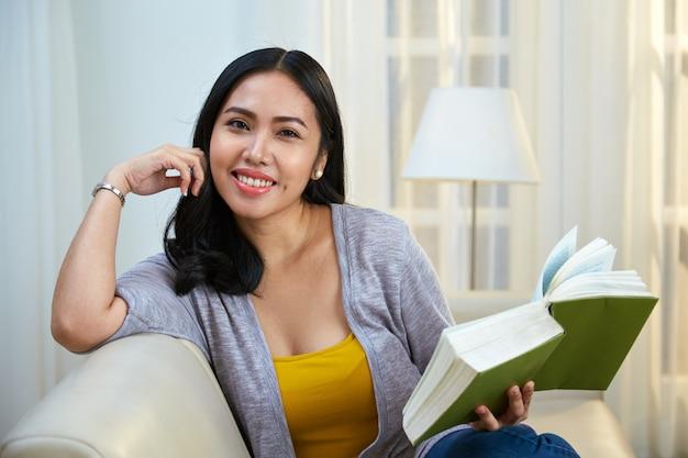 Filipijnse vrouw met boek camera kijken Gratis Foto