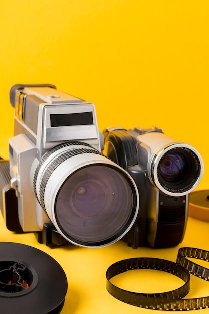 Filmstreep en camcordercamera tegen gele achtergrond Gratis Foto