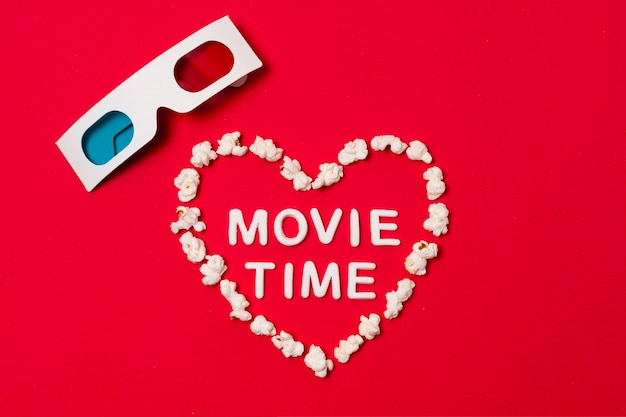 Filmtijd geschreven in hartvorm met 3d bril op rode achtergrond Gratis Foto