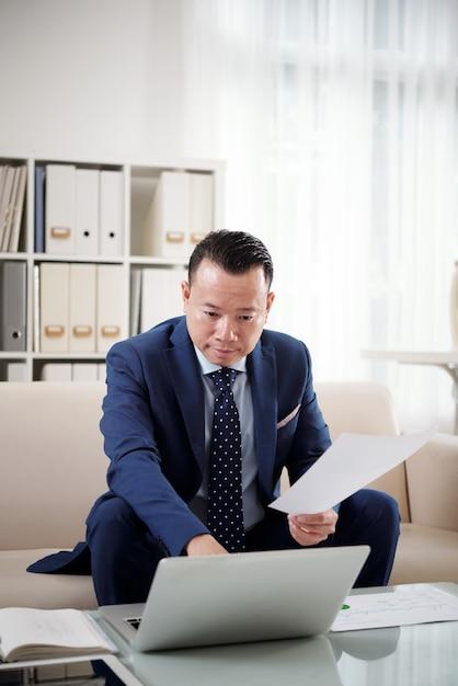 Financieel manager die rapport op zijn laptop voorbereidt dat naar documentatie van de afdruk verwijst Gratis Foto