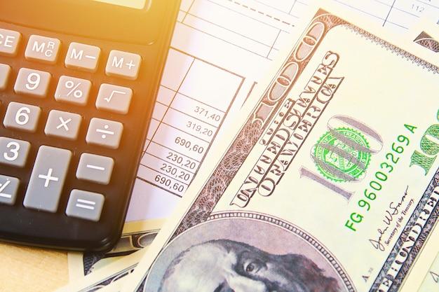 Financiën concept. verenigde staten honderd-dollarbiljetten, rekenmachine, rekeningen. Premium Foto