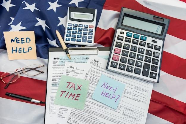 Financiën document 1040 belastingformulier met pen en rekenmachine op vlag van de vs. Premium Foto