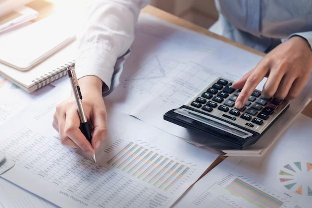 Financiën en boekhoudingsconcept. zakenvrouw werken op bureau met behulp van calculator Premium Foto