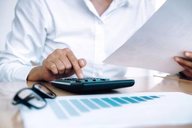Financiën sparen economie concept. vrouwelijke accountant of bankier gebruik rekenmachine. Gratis Foto