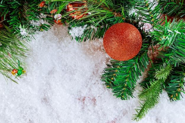 Fir kerstboom sneeuw met tak dennenappel, sneeuwvlokken op decoratie bal Premium Foto