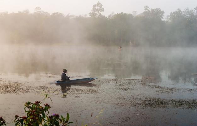 Fisheman zit op de boot en zoekt vissen in de rivier Premium Foto