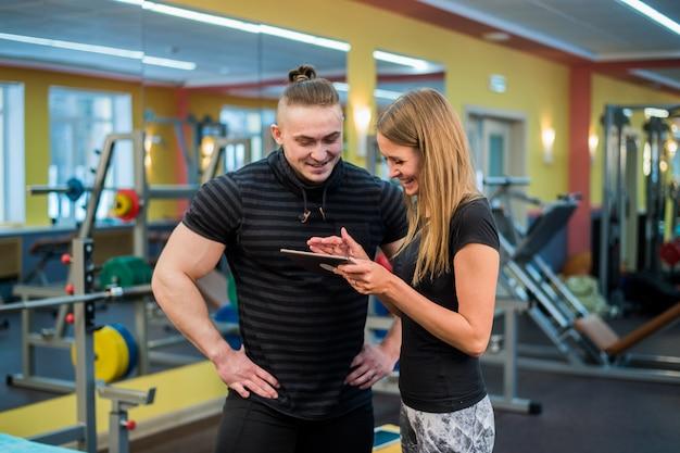Fit aantrekkelijke jonge paar in een sportschool kijken naar een tablet-pc als ze hun voortgang en fitness volgen Premium Foto