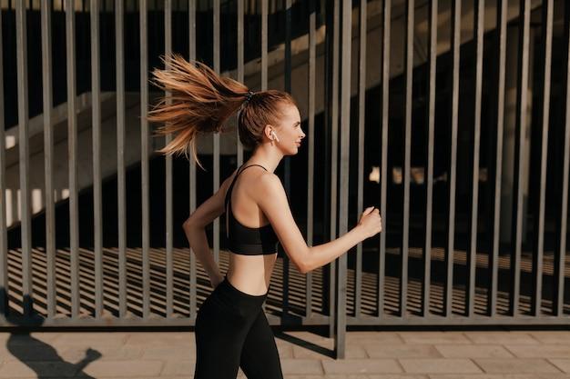 Fit aantrekkelijke jonge vrouw buitenshuis te oefenen. gezonde jonge vrouwelijke atleet fitnesstraining in zonnige warme dag. Gratis Foto