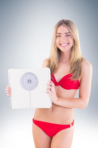 Fit blonde in rode bikini met schalen Premium Foto