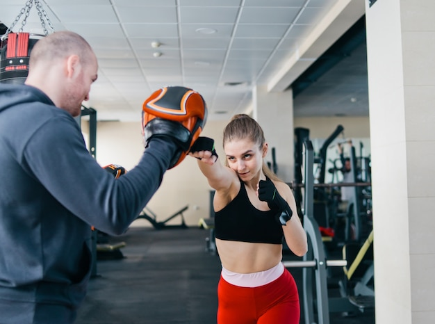 Fit blonde vrouw training punch met man trainer. in de sportschool. paar oefenen ponsen Premium Foto