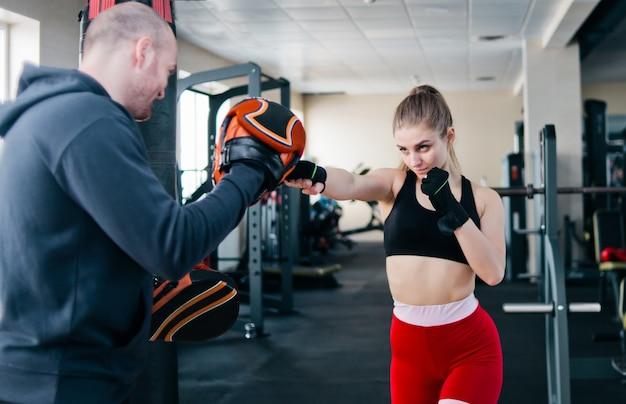 Fit blonde vrouw training punch met man trainer Premium Foto