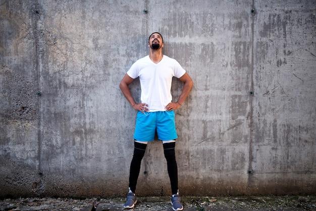 Fit en aantrekkelijk sporters tegen betonnen muur achtergrond luisteren naar muziek en opzoeken Gratis Foto