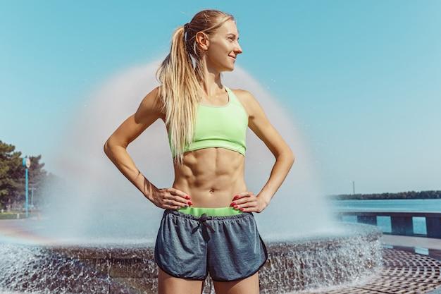 Fit fitness vrouw poseren in de stad Gratis Foto