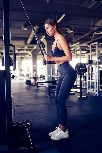 Fit goedgetrainde vrouw training triceps gewichtheffen in de sportschool. atletische sexy vrouw die oefening doet die machine in gymnastiek gebruikt - zijaanzicht. Premium Foto