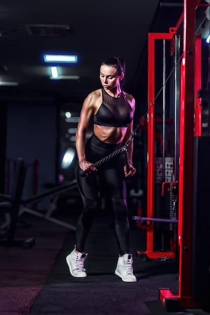 Fit goedgetrainde vrouw training triceps gewichtheffen in de sportschool. atletische sexy vrouw die oefening doet die machine in gymnastiek gebruikt Premium Foto