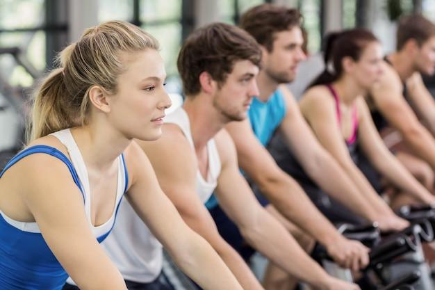 Fit groep mensen met behulp van hometrainer samen in de sportschool Premium Foto