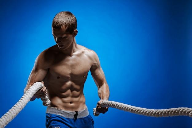 Fit jonge man met mooie romp en een touw op blauw Gratis Foto