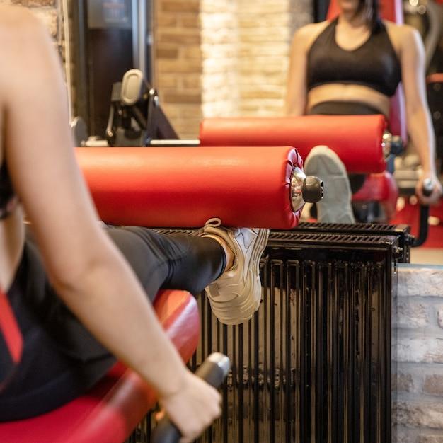 Fit jonge vrouw been presses in de sportschool doen Premium Foto