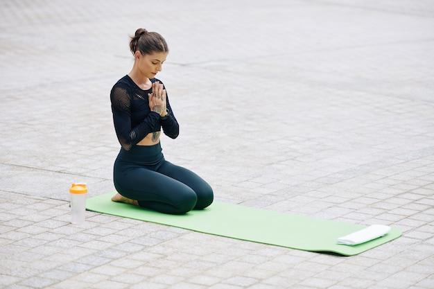 Fit jonge vrouw buiten mediteren op yoga mat. ze zit met gesloten ogen en houdt haar handen in mudra Premium Foto