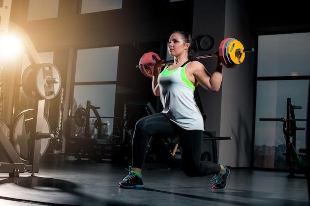 Fit jonge vrouw tillen halters op zoek gericht, uit te werken in een sportschool Gratis Foto