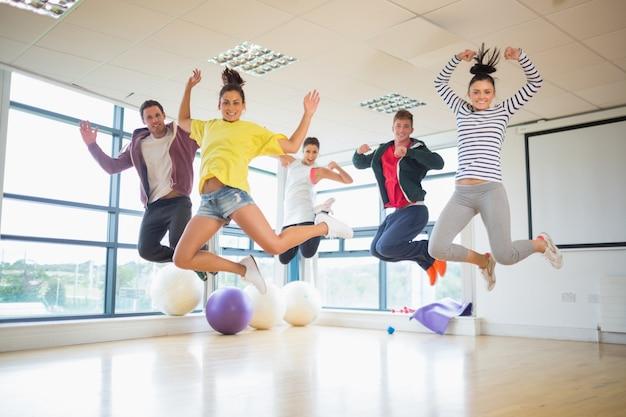 Fit mensen springen in lichte fitnessruimte Premium Foto