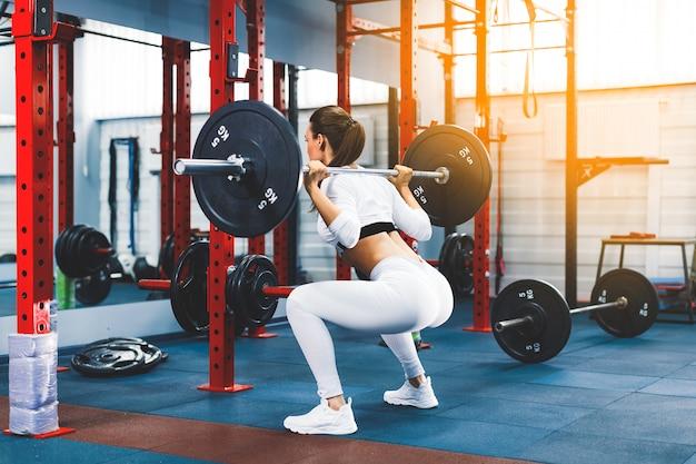 Fit mooi meisje doet squats met barbell in gym Premium Foto