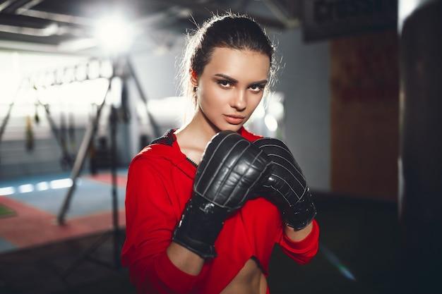 Fit slanke jonge mooie brunette vrouw boksen in sportkleding. donker zwak licht. Premium Foto