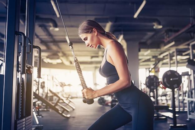 Fit vrouw training triceps tillen gewichten in de sportschool. atletische sexy vrouw die oefening doet die machine in gymnastiek gebruikt. Premium Foto