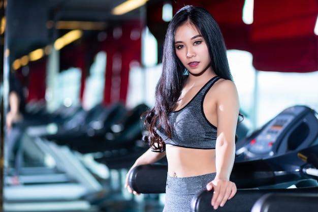 Fitness aziatische vrouwen die doen oefeningen die de run op de loopband in het interieur van de sportgymnastiek en de gezondheidsclub trainen. Premium Foto