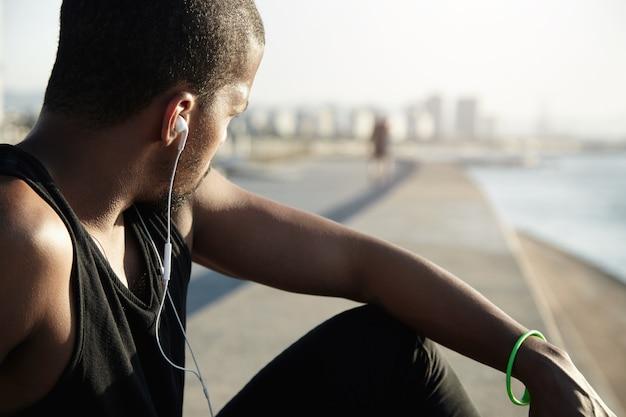 Fitness en een gezonde levensstijl concept. terug schot van atleet rust na training in de open lucht. jogger met donkere huidskleur in zwart a-shirt die opzij kijkt en luistert naar meditatieve geluiden in oortelefoons Gratis Foto