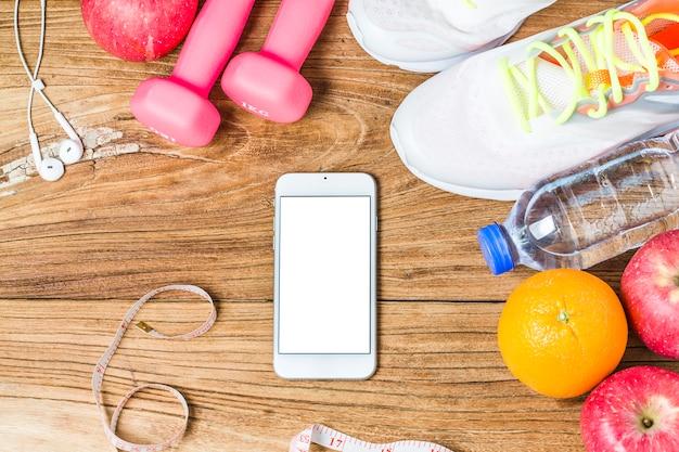 Fitness, gezonde en actieve levensstijl concept, fles water, domoren, sportschoenen, smartphone met koptelefoon en appels op houten achtergrond. kopieer ruimte voor tekst. bovenaanzicht Gratis Foto