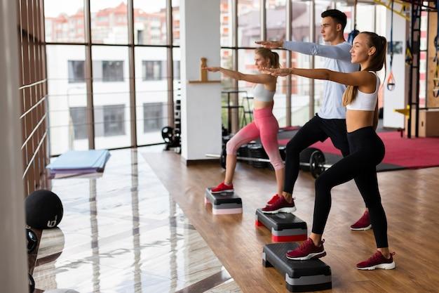 Fitness groepsles op sportschool met atletische jongeren Gratis Foto