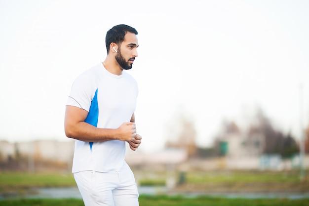 Fitness. jonge man loopt in stedelijke omgeving Premium Foto