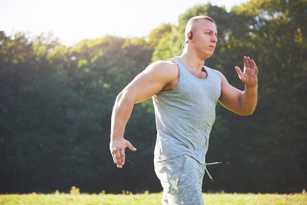 Fitness man atleet joggen in de natuur tijdens zonsondergang. Gratis Foto
