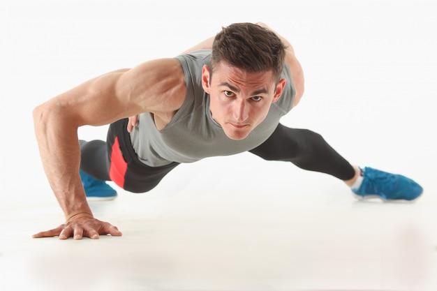 Fitness man wringen van de vloer toont goede fysieke oefeningen op een witte achtergrond gezonde levensstijl voor veel mensen oefenen hun eigen gewicht voor verliezen voor elke dag push-up. Premium Foto