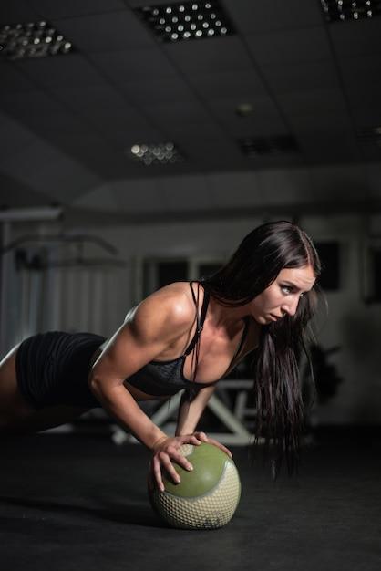Fitness meisje doet push-ups op de bal Premium Foto