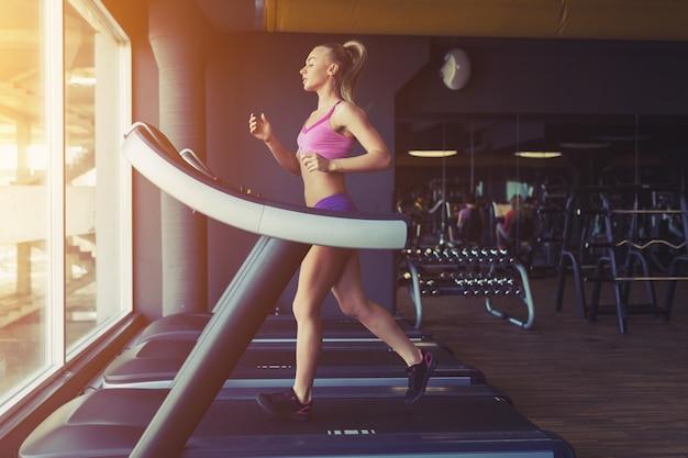 Fitness meisje draait op loopband Gratis Foto