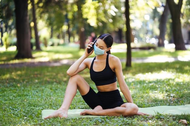 Fitness meisje met een smartphone op natuur achtergrond, geniet van sportopleiding. vrouw die mobiel buitenshuis gebruikt. Gratis Foto
