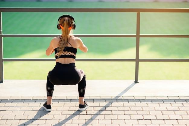 Fitness meisje met oortelefoons die hurkende oefeningen met stoffen buitband doen tijdens haar sporttraining op speciale sportgrond Premium Foto